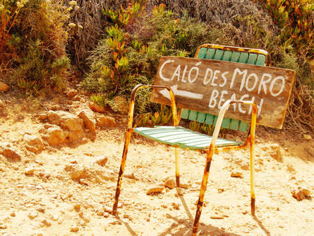 Cal? des Moro beach hand written sign on a rusty chair showing direction to the most popular beach of Mallorca