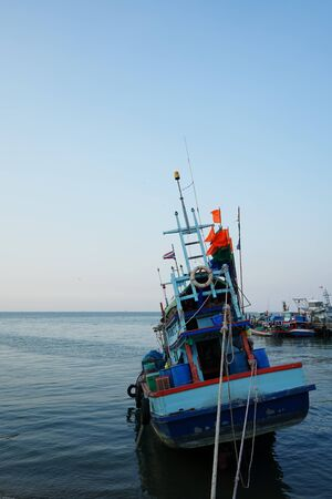 A fishing boat held by ropes facing towards vastness of sky and sea. Shot from behind. 版權商用圖片
