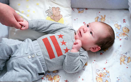 fondness: Charming baby in infant bed have eyes on his mother and hold mother by the hand