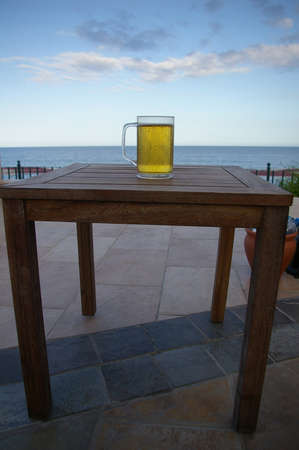 disposed: A glass of the cold beer on the table disposed on the outdoor patio, seascape and the cloudy sky are in the background
