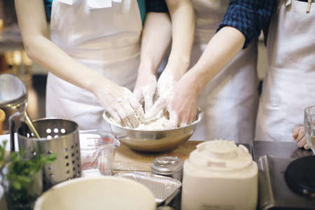 beating: Hands of a man and a woman beating dough togetherat the kitchen.