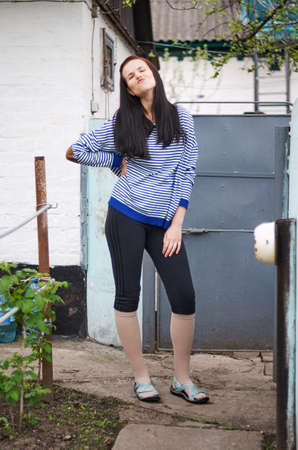 brune: Lovely young woman, wearing in striped jacket, sports trousers and sandals Posing near wall and gate at the backyard Stock Photo