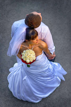 newly wedded couple: Newly wedded couple leaning back to back and hold hands. Bride with a bouquet of yellow white red flowers. Outdoor shot