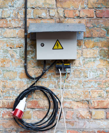 switch plug: Outdoor Electric control cabinet for electrical equipment on brick wall with wires and plug jack. Knife switch on old dirty wall
