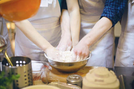 beating: Hands of a man and a woman beating dough together Stock Photo