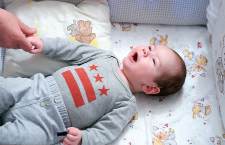 fondness: Charming baby in infant bed have eyes on and hold mother by the hand Stock Photo