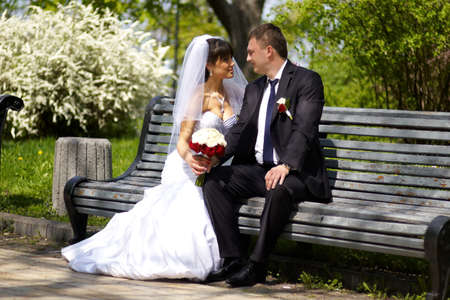 a newly married couple: A newly married couple sin on the bench hold hands with bouquet of flowers and look with eyes full of love at each other.