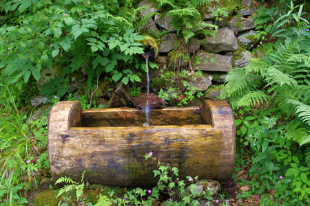 Decorative fountain with potable water in the Vosges mountains in France, Alsace. mountain waterfall Stock Photo