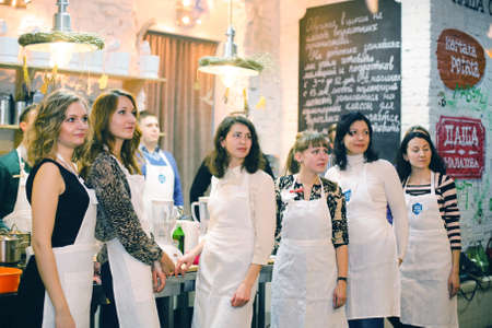 KYIV, UKRAINE - December 13, 2014: Happy group of friends with male chef cook cooking and talking in kitchen. Cooking class. Editorial