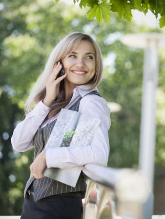 Young beautiful business woman entrepreneur in business suit talk by phone outdoor. Female work,negotiating,solves problems,dials,talking on smart phone