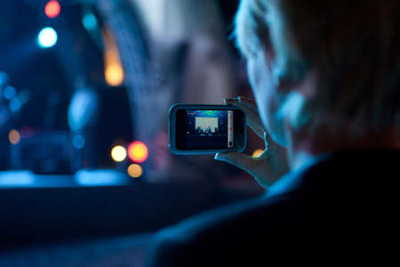 La mujer utiliza el teléfono móvil de disparo de vídeo de fotos de concierto en frente de la etapa en la noche con bokeh borrosa hermosa de las luces en el fondo Foto de archivo - 69649977