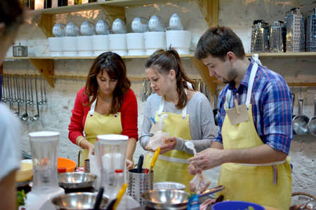 KYIV, UKRAINE - December 13, 2014: Happy group of friends with male chef cook cooking and talking in kitchen. Cooking class. Redakční