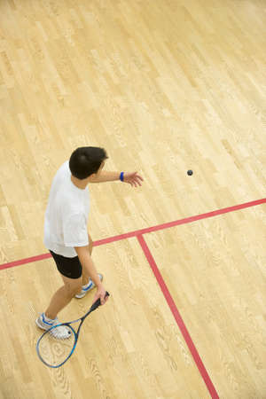 Squash player in action on squash court, back view.Two men playing match of squash.