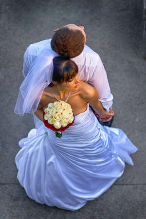 Newly wedded couple leaning back to back and hold hands. Outdoor shot of a Bride with a bouquet of yellow white red flowers. Reklamní fotografie