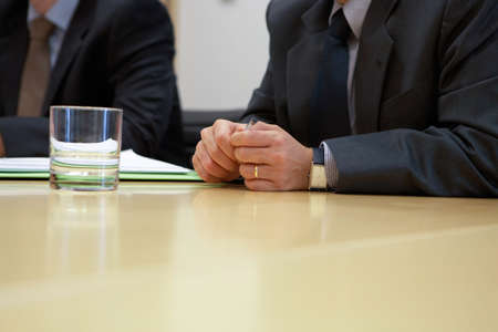 Businessman sitting at the desk and holding pen in hands.Business people working around table in office.Business planning,teamwork,collaboration,corporate concept Reklamní fotografie