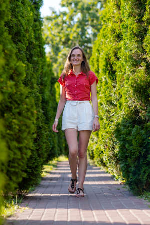 Portrait of young smiling woman in white short and red blouse walking in summer park, outdoors