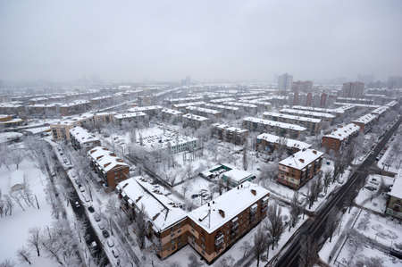 The aerial View of residential district in dusky winter day.View over the city rooftops with sunlight and snow.Moderns buildings at Industrial uptown, residential neighbourhood. Kiev,Ukraine