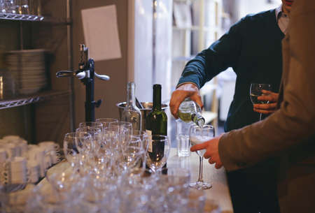 Caucasian man pouring white wine from bottle into wineglass in a bar.Wine tasting and celebration concept