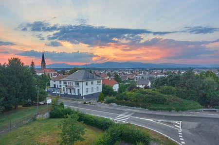 Panoramic view on settlement in Alsace,France,road and Vosges mountain at sundown.Roofs of the city from top.Beautiful landscapeBeautiful view of church and red roofs of small town in Alsace