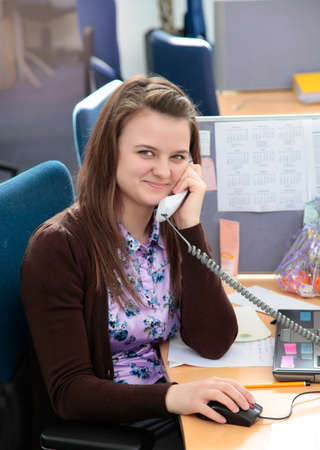 Cheerful young beautiful woman italking on the phone and looking at camera with smile while sitting at her working place.Female work,negotiating,solves problems,dials,talking on phone concept Reklamní fotografie