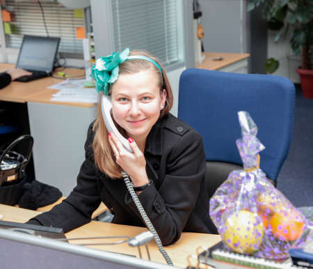 Cheerful young beautiful woman talking on the phone and looking at camera with smile while sitting at her working place