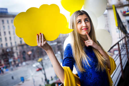 Beautiful girl stand on the building background with toy balloons holds a yellow plate. Space for text or message