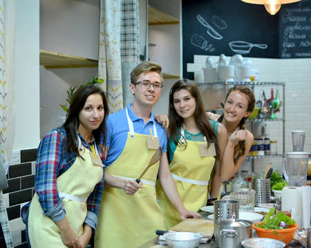Group of three women and one man cooking and talking in the kitchen. Culinary, food and people, cooking class concept Reklamní fotografie