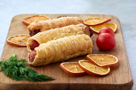 Baked sausages wrapped in puff pastry on a wooden cutting board accompanied by parsley,tomatoes and dried orange slices.Pigs in blanket,sausage rolls Reklamní fotografie
