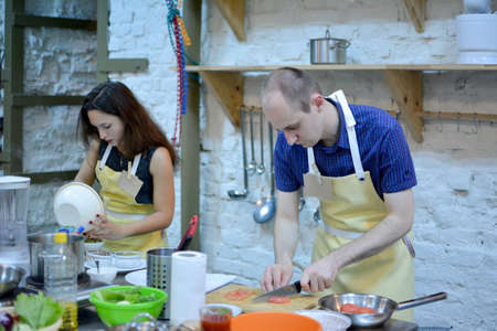 Two happy man and woman cooking and talking in the kitchen. Culinary, food and people, cooking class concept Reklamní fotografie