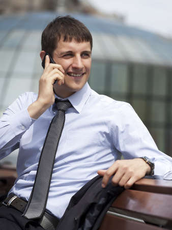 Portrait of a handsome business man sitting on a bench and talking on mobile phone.Closeup of serious successful man in a suit talking on cell phone outdoor