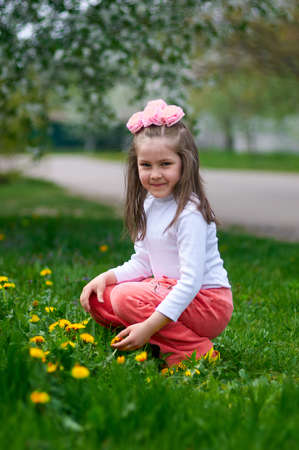 A cute girl sitting on the green lawn with yellow flowers