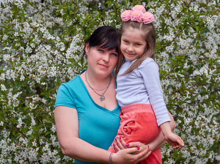 Portrait of a mother and a little daughter near the blooming cherry tree. Mother hugs daughter,happy family