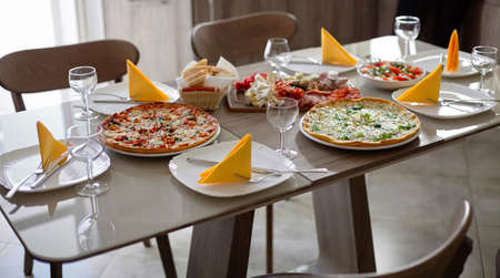 Beautifully decorated table with cheese and pepperoni pizzas, snacks, appetizers and vegetable salad.Serving table