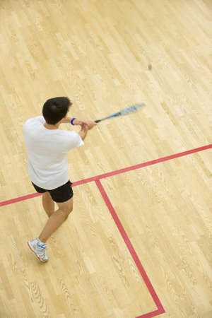 Squash player in action on squash court, back view