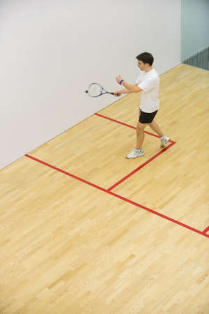 Squash player in action on squash court, side view