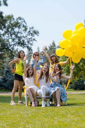 Group of beautiful young female friends posing outdoor with yellow balloons.Young women sitting on a bench and having fun Reklamní fotografie