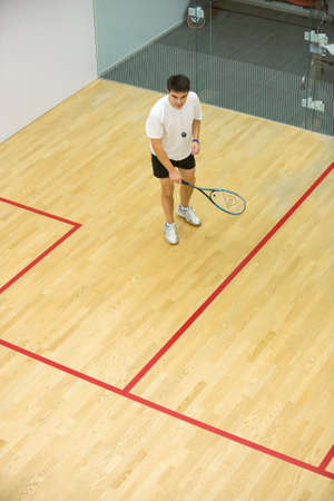Squash player in action on squash court, front viewYoung man playing match of squash