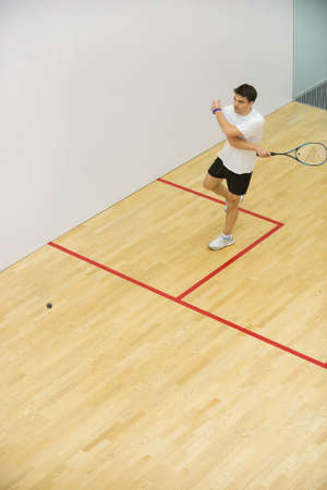 Squash player in action on squash courtYoung man playing match of squash
