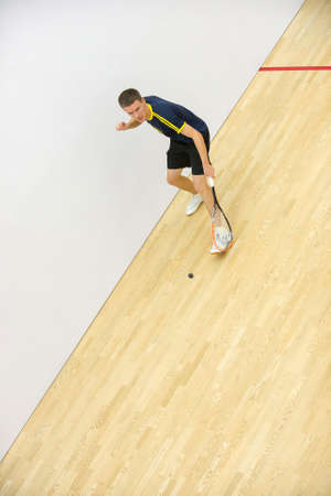 Squash player in action on squash court, front view