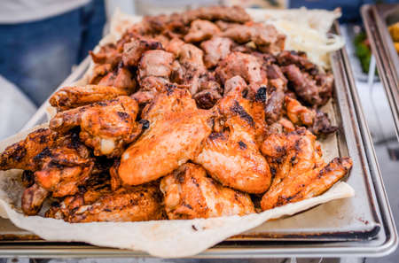 Barbecue roasted tasty chicken wings with herbs and sauce on the tray. Outdoors Food Reklamní fotografie