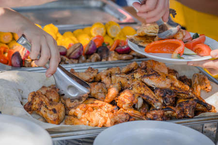Hand picks the barbecue roasted tasty chicken wings with herbs and sauce from the tray. Outdoors Food.Buffet self-service food