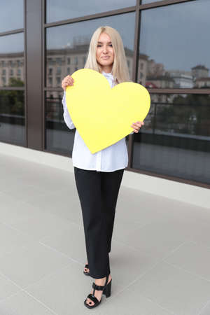 Beautiful girl in white blouse and black trousers stand against the office building background holds a heart-shaped yellow plate, Empty space for text or message