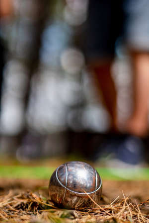 Close up of metallic petanque ball on the ground against the blurred background.Sport, relax, recreation and leisure concept