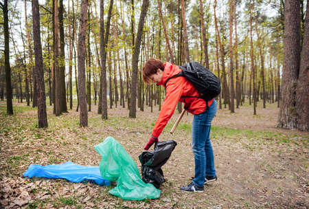 Woman volunteer collecting garbage in park