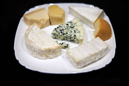 Pieces of different types of cheese on white plate Stock fotó - 136487917