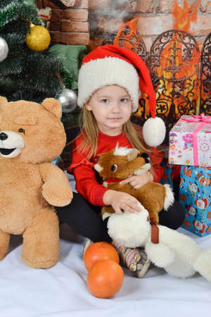 Cute little girl in Santa Claus hat with Christmas presents