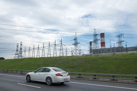against the current: Electricity high voltage towers images and road with car Stock Photo