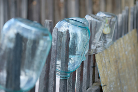 glass fence: Large glass jars on a wooden fence. Selective focus