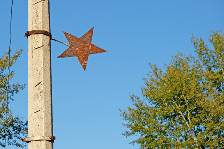 Old rusty metall star on the sky background