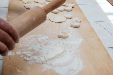 flattened: Dough being flattened on a wooden cutting wooden board. Selective focus